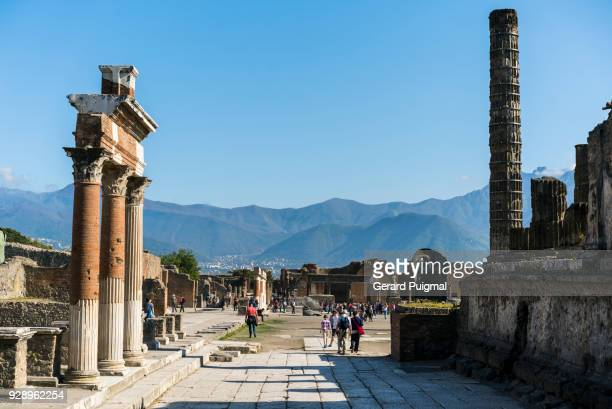 One of the main paths in the Roman city of Pompeii with tourists walking by(Pompei, Campania, italy)