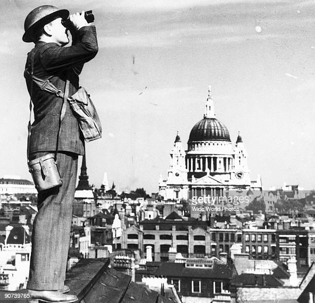 'One of the many City of London raid 'spotters' on duty during an air raid warning in London Many large city businesses instead of closing down when...