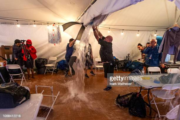One of the members of the media cuts a whole in the ceiling of the press tent as they evacuated the media just before the start of Florida Democratic...
