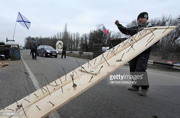One of the men who called themselves members of local militia carries a makeshift road spike barrier to block a highway that connect Black Sea Crimea...