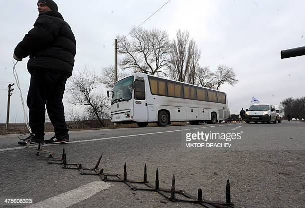 One of the men who called themselves members of local militia used a road spike barrier to block a highway that connect Black Sea Crimea peninsula to...