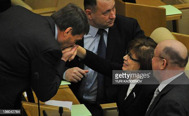 One of the newly elected lawmakers kisses hand of his colleague threetime Olympic figure skating champion Irina Rodnina before the first session of...