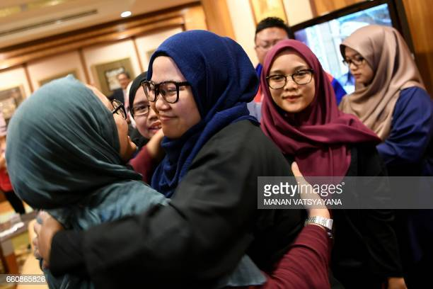 One of the nine returning Malaysian national hugs her family members upon arriving at the Bunga Raya complex at Kuala Lumpur International Airport in...