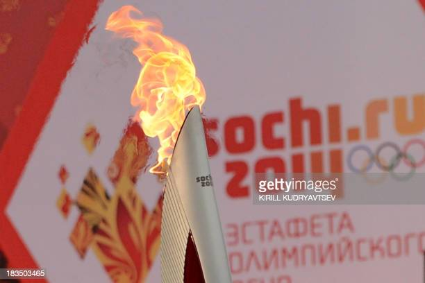 One of the Olympic torches rises in front of a poster with the Sochi 2014 Winter Olympic logo just outside the Red Square in Moscow on October 7...