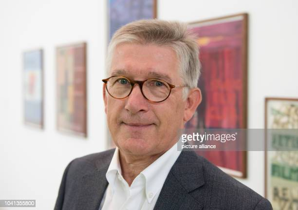 One of the owners of the Viehof collection Eugen Viehof stands in front of artworks by the Scottish artist Petert Doig in the exhibition 'Viehof...
