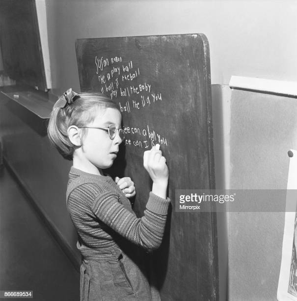 One of the pupils of South Mead School, Southfield, Wimbledon seen here practising hand writing on the blackboard, 14th January 1954.