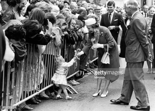 One of the Queen's tinier subjects hands over a posy in Welshpool 12th July 1986
