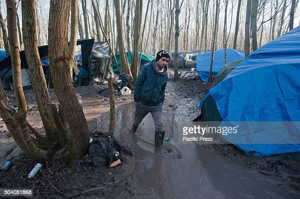 One of the refugees from the refugee camp in Dunkirk walks through the mud at the refugee camp in Dunkirk where water flooded most of the tents after...