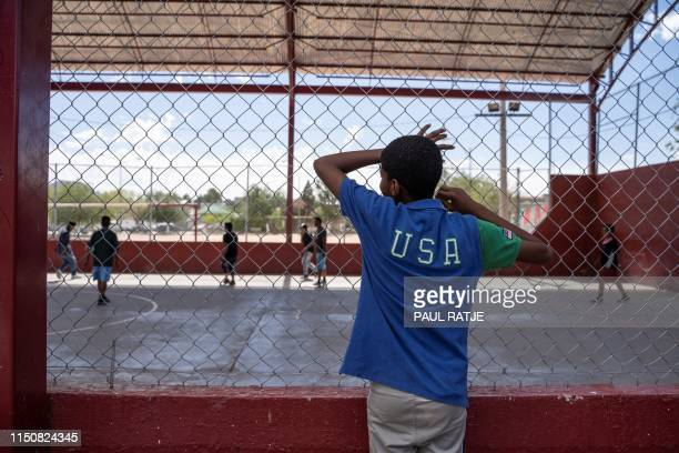 TOPSHOT One of the residents of Iglesia Metodista El Buen Pastor migrant shelter watches the soccer match at a park near the shelter on June 09 2019...