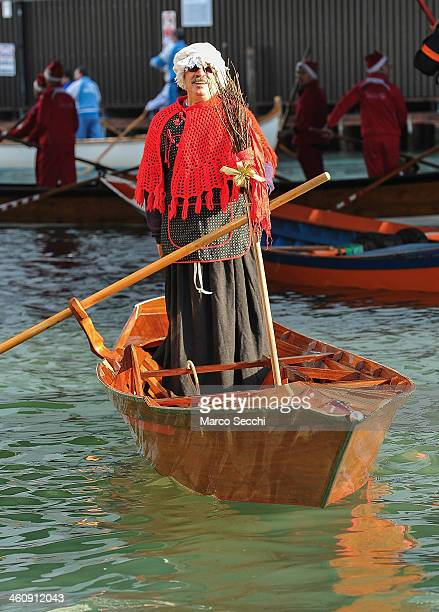 One of the rowers dressed in costume sails on the Grand Canal at the end of the Befana Regatta on January 6 2014 in Venice Italy In Italian folklore...