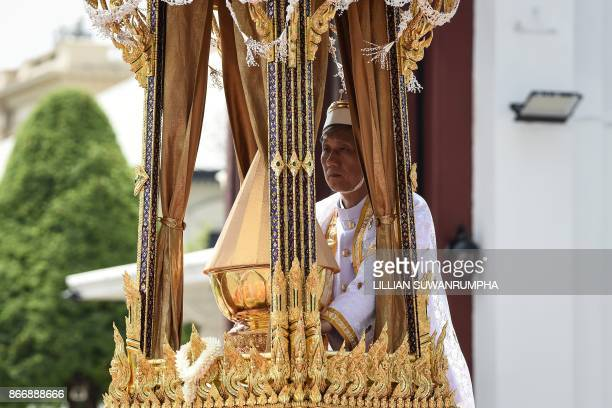One of the royal doctors holds an urn containing the ashes of the late Thai king Bhumibol Adulyadej atop a royal chariot during the funeral...