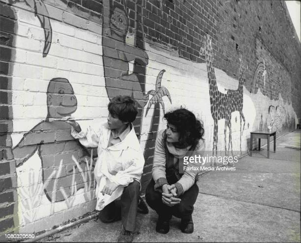 One of the school children 11 yr old Allen Floyd puts the finishing touches to the mural watched by the schools Arts and Crafts teacher Miss Sue...