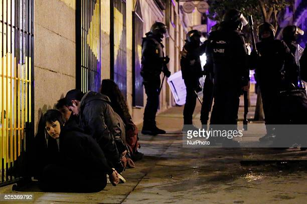 One of the six protestors arrested and handcuffed looks at riot police during a protest against the 'Clamp law' in Madrid Spain Saturday 8th february...