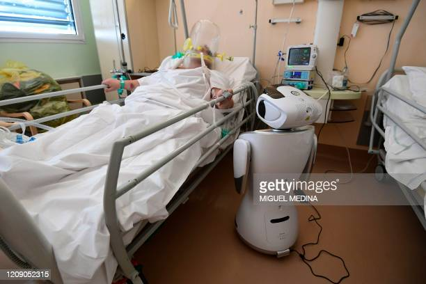 One of the six robots of the Circolo di Varese hospital stands near a patient, on April 3 to help the healthcare staff of the High Intensity Medicine...