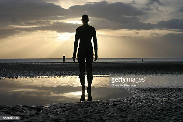 One of the sixfoot bronze figures by British artist Anthony Gormley which are situated on the sands at Crosby by Liverpool Merseyside The local...