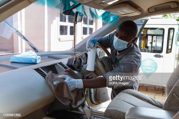 One of the staff member of Wash Me Please Mobile Carwash seen sanitizing a clients car after washing it at home in Kiambu. The wash me please is a...