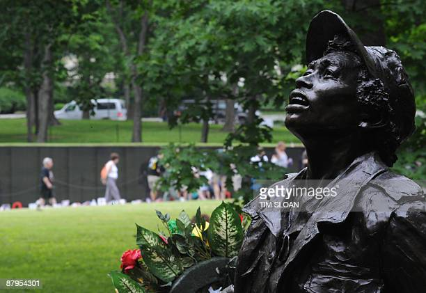 One of the statues that makes up the Vietnam Women's Memorial is seen with the National Vietnam Veterans Memorial Wall in the background during the...