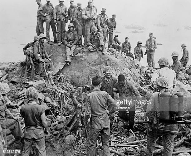 One of the ten prisoners taken on Iwo Jima in the Volcano Islands is being brought back to the beach by 3rd Division Marines ca February 19 March 17...