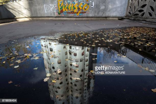 One of The Tours Aillaud towers also known as Tours Nuages reflects in a puddle on November 23 2017 in Nanterre near Paris A symbol of the great...