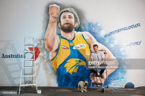 One of the two artists Jacob Butler poses with Banjo the French Bulldog in front his Josh Kennedy 2018 Mural commissioned by Seven West Media and the...