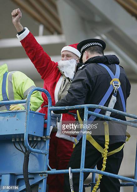 One of the two campaigners is led away after scaling the new Scottish Parliament building Holyrood on November 30 2004 in Edinburgh Scotland The two...
