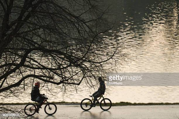 One of the two cyclists is riding backwards near Vistula river On Sunday 21 January 2018 in Krakow Poland