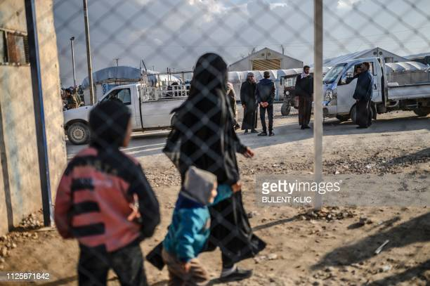 One of the two detained French women who fled the Islamic State group's last pocket in Syria walks with her child after speaking to a AFP reporter at...