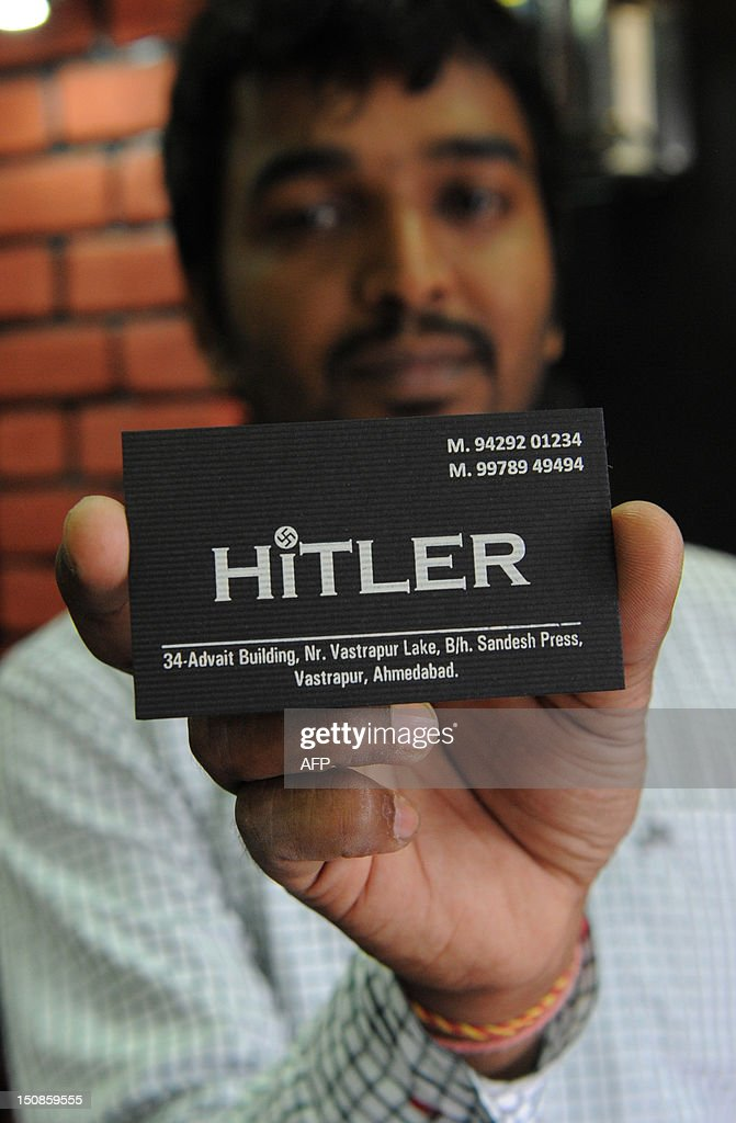 One of the two Indian owners of the 'Hitler' clothing store - Rajesh Shah - poses with a visiting card at his shop in Ahmedabad on August 28, 2012. Members of the Jewish community in the western Indian state have urged the shop owners to change the name of the store, which was opened on August 19, 2012. Prior to this a banner with the wording 'Hitler opening shortly' was used by Shah and his co-owner to publicise the opening of the shop. AFP PHOTO/Sam PANTHAKY