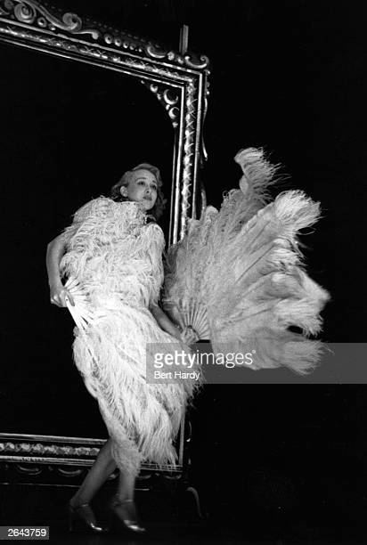 One of the Windmill Girls from Vivian Van Damm's 'Revudeville' performing with ostrich feathers at the Windmill Theatre London Original Publication...