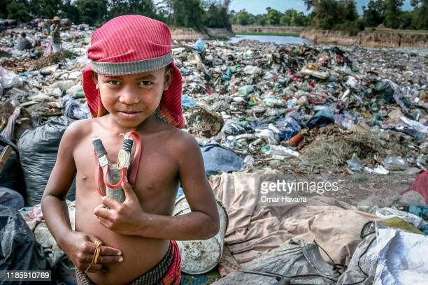 One of the youngest inhabitants of the Anlong Pi dump shows his home-made slingshot on January 06, 2011 near Siem Reap, Cambodia. Slingshots are used...