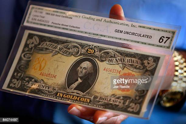 One of three sequential $20 gold certificate notes from 1905 featuring George Washington is displayed on sale at the Arcade Currency Palace December...