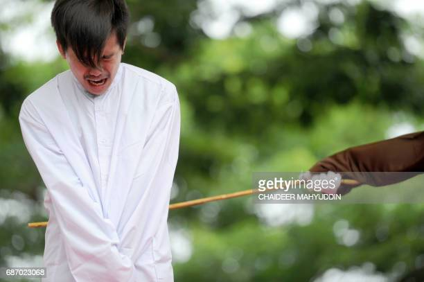 TOPSHOT One of two Indonesian men is publicly caned for having sex in a first for the Muslimmajority country where there are concerns over mounting...