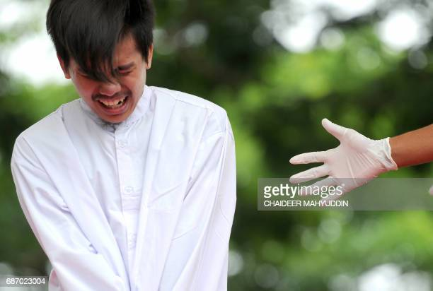 One of two Indonesian men reacts as he is publicly caned for having sex in a first for the Muslimmajority country where there are concerns over...