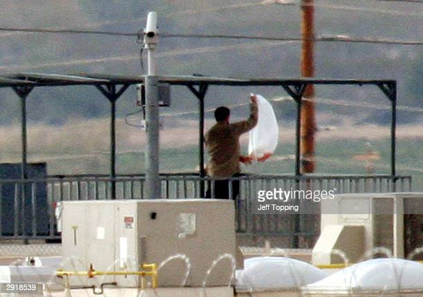 One of two inmates holding a hostage at the State Prison ComplexLewis holds a bag on the observation deck of a guard tower wearing a guard's shirt...