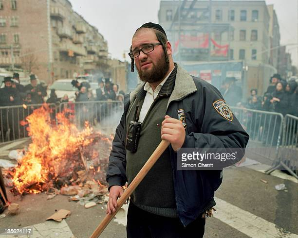 """One of Williamsburg's """"Shomrim"""", or religious neighborhood watchmen, tends to a fire and barricades as members of the community cast their religious..."""