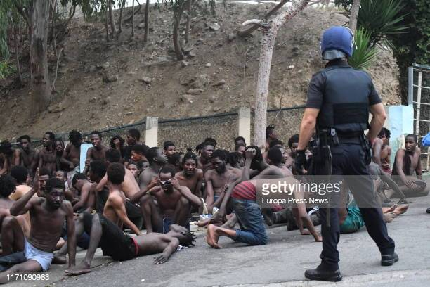 One officer of the National Police is seen with some of the 153 migrants who have jumped the fence of Ceuta at the first incursion of the year on...