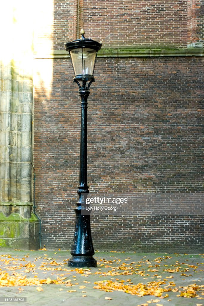 One old Dutch lamppost on corner of cobbled street : Stock Photo