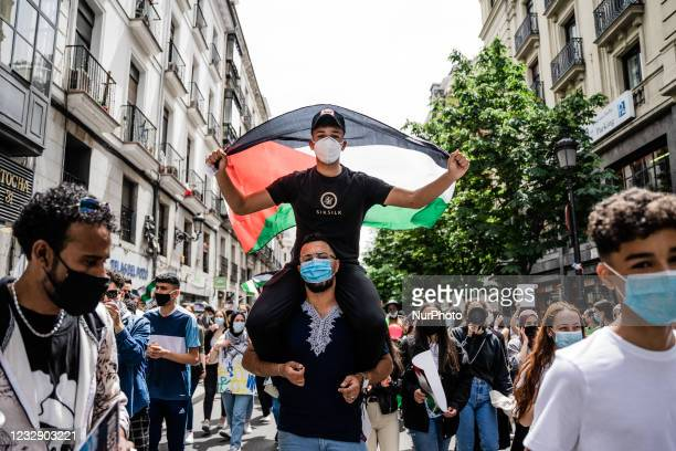 One on her shoulders holds a Palestinian flag as protesters sing songs of support for Palestine and against Israel in Madrid, Spain, on May 15 on the...