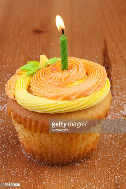 One orange and yellow decorated cupcake with burning candle