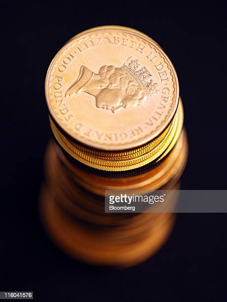 A UK one ounce one hundred pound gold coin sits on a stack of gold coins in this arranged photograph at Gold Investments Ltd bullion dealers in...