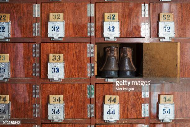 one pair of shoes in a shoe locker with an open door. lockers in a row, with numbers. - 余暇施設 ストックフォトと画像