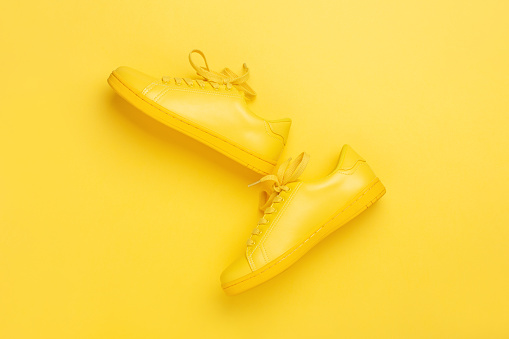 One pair of yellow shoes on yellow background. 969878700