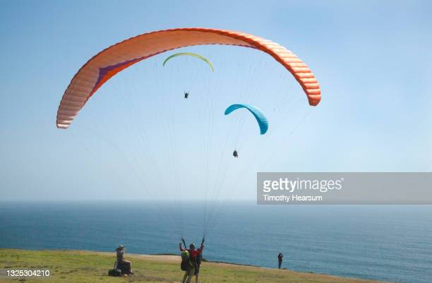 one paraglider preparing to take off and join two others already in the air; ocean and blue sky beyond - timothy hearsum fotografías e imágenes de stock