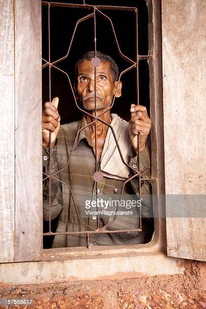 One Pensive Senior Rural Indian man looking from window
