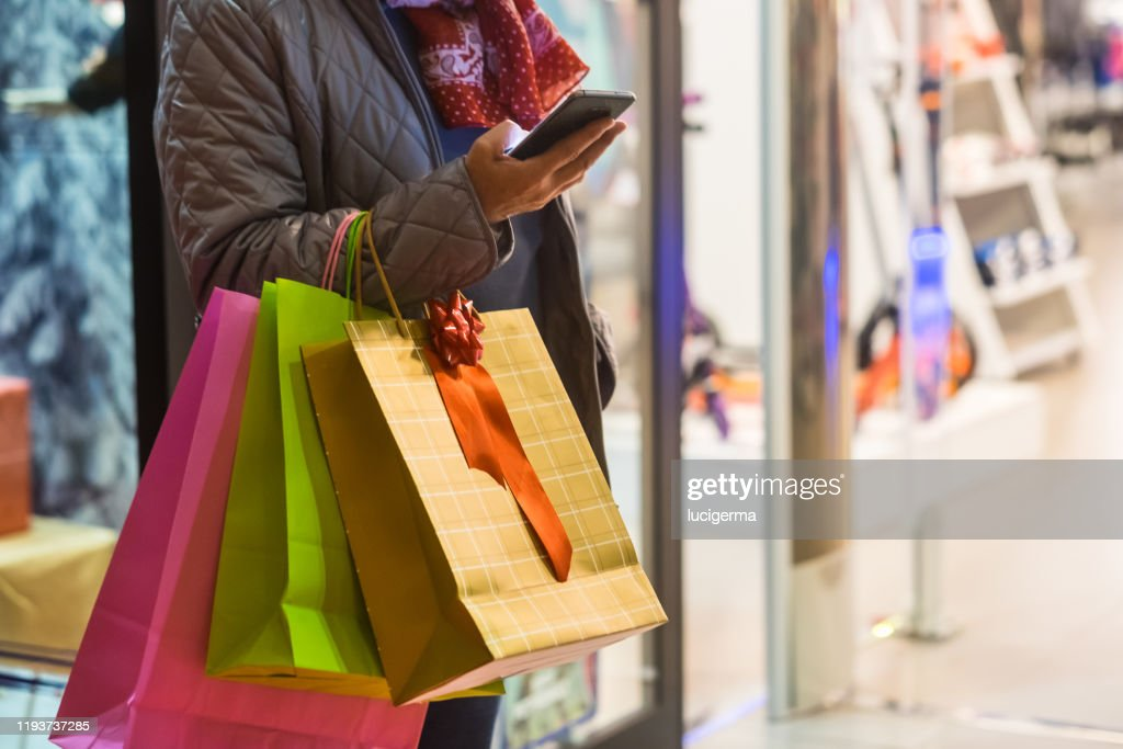 One people alone. A senior woman enjoys evening shopping while taking advantage of offers and discounts. On his arm a lot of shopping bags while she looks at her cell phone : Stock Photo
