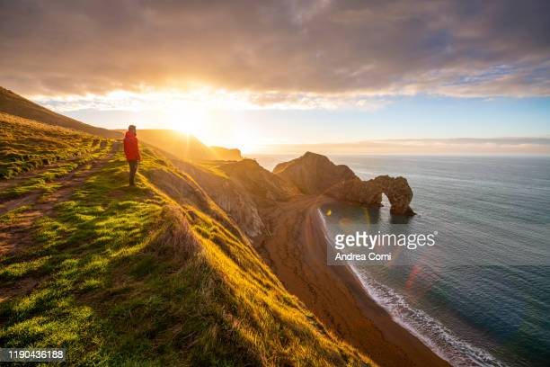 one person admiring the durdle door at sunrise, dorset, england - coastline stock pictures, royalty-free photos & images