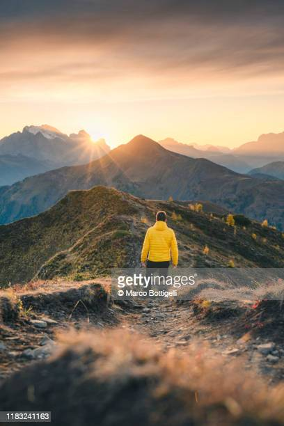 one person admiring the sunset on a mountain ridge, italy - wide shot stock pictures, royalty-free photos & images