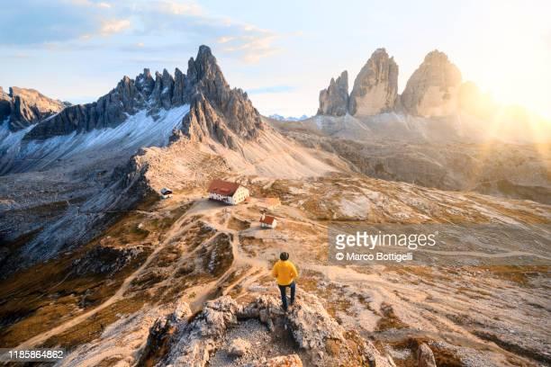 one person admiring the three peaks of lavaredo and the dolomites, italy - トレチーメディラバレード ストックフォトと画像