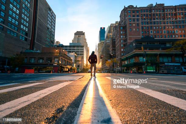 one person crossing a junction in manhattan at sunrise, new york city - stadtzentrum stock-fotos und bilder