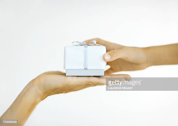 One person handing second person gift, close-up of hands